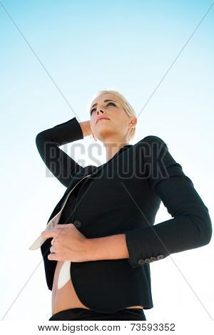 young blue eyes woman with short blonde hair in black blazer outdoor city portrait
