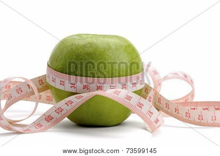 A green apple and a measuring tape isolated on white background.