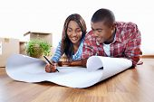 stock photo of family planning  - new home plans for young african black couple in apartment - JPG