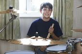 picture of drum-kit  - Portrait Of Boy Playing Drum Kit At Home - JPG