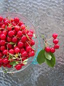 picture of dimples  - Freshly picked tart cherries in a glass bowl on a glass table - JPG