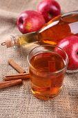 picture of sackcloth  - Apple cider with cinnamon sticks and fresh apples on sackcloth background - JPG