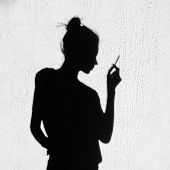 stock photo of teen smoking  - Shadow of sad girl with cigarette smoking around on wall background