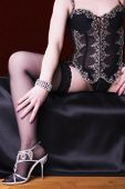 stock photo of thigh highs  - Sexy unrecognizable young woman sits on bed - JPG