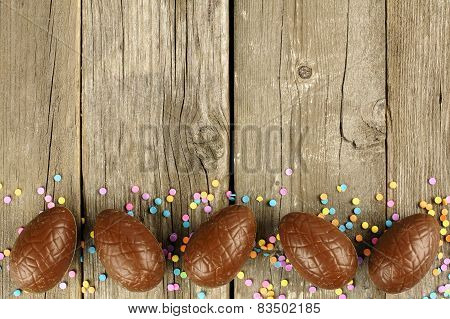 Chocolate Easter egg border on wood