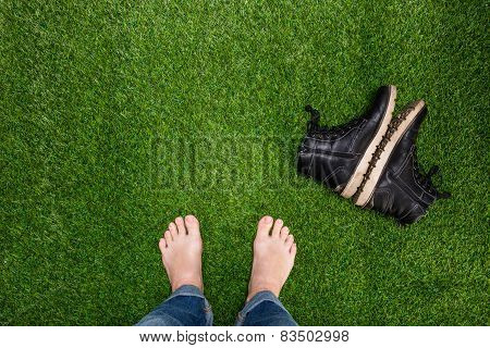 Mens Feet Resting On Grass With Lying Boots