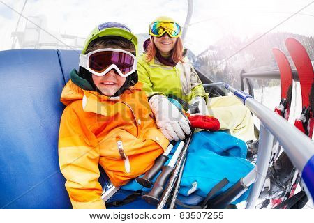 Happy little boy with mom, mountain ski chair lift