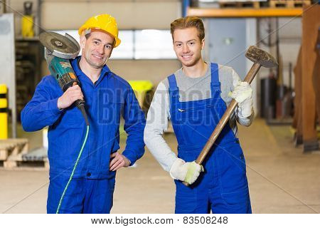 Two Steel Construction Workers Posing With Angle Grinder And Hammer