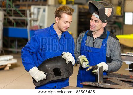 Instructor Teaching Trainee How To Weld Metal