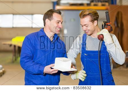 Two Steel Construction Workers Inspecting Metal Pieces