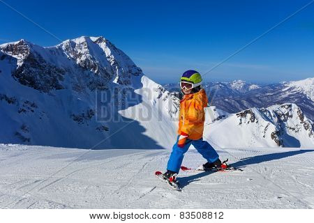 Boy in mask skiing with beautiful mountain view