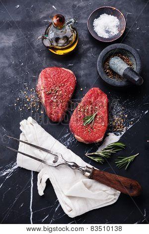 Raw Fresh Meat Rump Steak, Seasoning And Meat Fork On Dark Marble Background