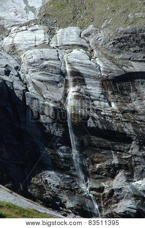 Waterfall In Rocky Valley Nearby Grindelwald In Switzerland