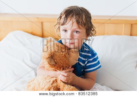 Cute toddler boy in a bed after shower, holding his teddy bear