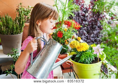 Adorable little girl watering flowers
