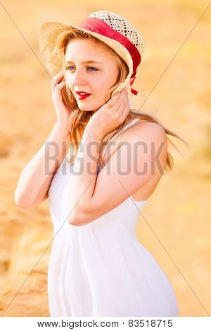 Lonely Beautiful Young Blonde Girl In White Dress With Straw Hat Posing At Golden Wheat Field