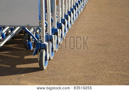 Row of luggage carts with advertisement space closeup view