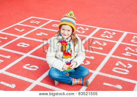 Outdoor portrait of a cute little girl wearing colorful hat, scarf and boots, resting on playground