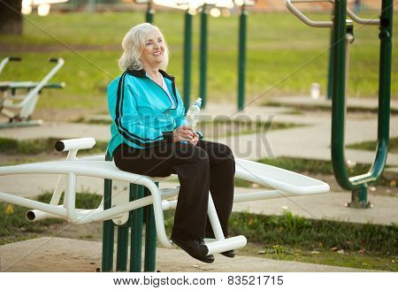 Senior Woman Resting After Exercises Outdoors