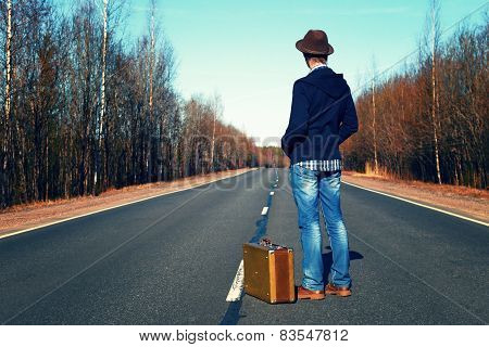 Trip to holiday. Travel to a week-end.The man in jeans with a suitcase.