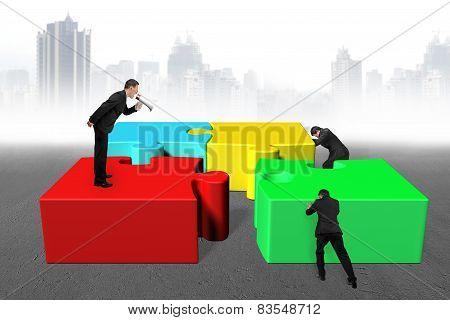 Businessman Using Megaphone Yelling Employees To Push Colorful Jigsaw Puzzle