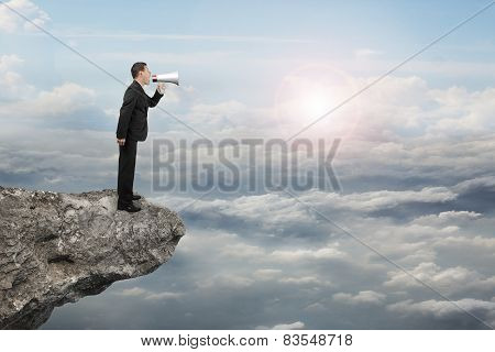 Businessman Using Megaphone Yelling On Cliff With Sunlight Cloudscape