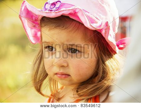 Cute little sad girl thinking in the park at summer day