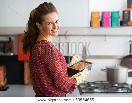 Happy Young Housewife Holding Baking Dish With Bread