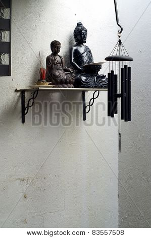 Two Buddhas On Shelf With Incense And Wind Chime