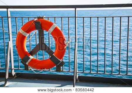 Red lifebuoy with rope on the ferry