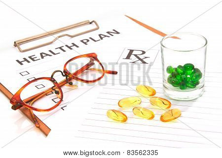 Glasses And Pill Capsules Resting On Health Plan Notes Or Patient Record Form