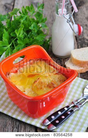 potato gratin, gratin dauphinois on a wooden table, french cuisine