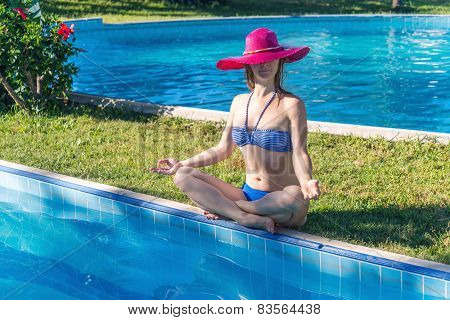 Woman meditating at the pool