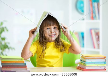 smiling child with a book over her head
