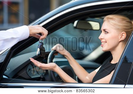 Car dealer giving keys to happy woman