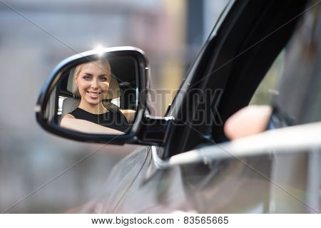 Young woman looking at car sideview mirror