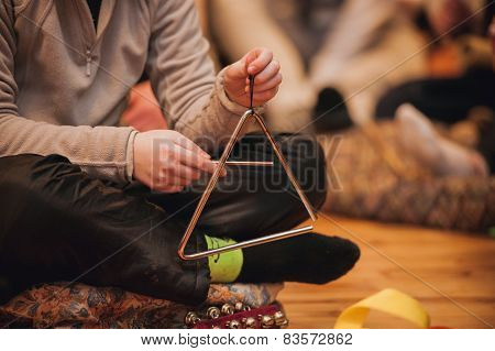 Girl Playing A Musical Triangle