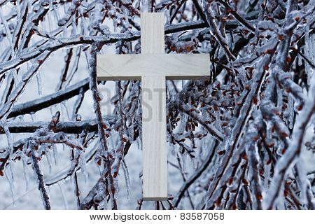 Wooden cross hanging in branches of ice covered tree