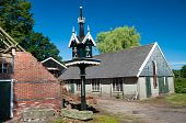 stock photo of pigeon loft  - new dovecote in front of an old barn and a decayed farm - JPG