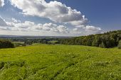 picture of cloud forest  - beautiful summer rural landscape with green meadow in foreground forests villages in background and blue sky with white clouds above - JPG