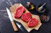 stock photo of red meat  - Raw fresh marbled meat Steak and seasonings on dark marble background - JPG