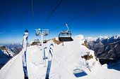 pic of caucus  - Ski lift chairs and skies over the mountain peak with piste bellow on sunny winter day - JPG