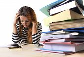 stock photo of stress  - young stressed student girl studying pile of books on library desk preparing MBA test or exam in stress feeling tired and overwhelmed in youth education concept - JPG