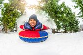 foto of snow forest  - East Asian boy on snow tube in winter with snow splash during day in the fir tree forest - JPG