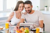 pic of newspaper  - Beautiful young couple bonding to each other and reading newspaper together while sitting in the kitchen and having breakfast - JPG