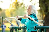 pic of 70-year-old  - 70 years old Senior Woman doing Exercises for Legs Outdoors in the Bright Autumn Evening - JPG