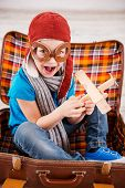 foto of little boys only  - Top view of happy little boy in pilot headwear and eyeglasses playing with wooden planer and smiling while sitting inside of briefcase - JPG