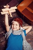 pic of little boys only  - Top view of happy little boy in pilot headwear and eyeglasses lying on the hardwood floor and playing with wooden planer - JPG