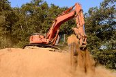picture of track-hoe  - Large track hoe excavator working on large dirt pile on a new commercial development construction project - JPG