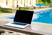 picture of work bench  - Laptop on a bench by the pool working on vacation with mobility concept - JPG
